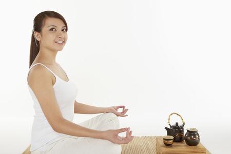 mat like: Woman sitting and meditating Stock Photo