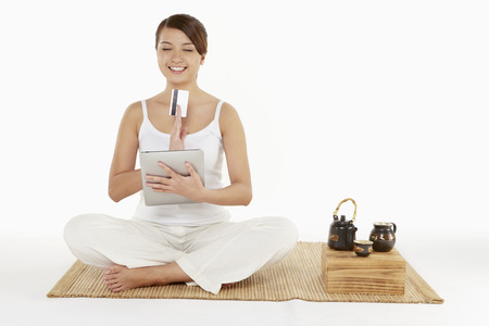 Woman sitting and meditating with digital tablet and credit card photo
