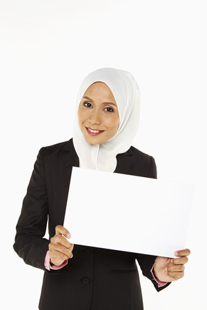 Businesswoman holding up a blank placard photo