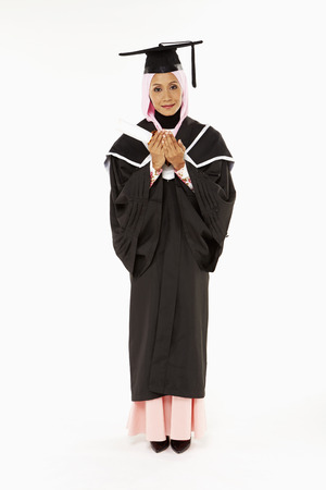 Woman in graduation robe, praying Stock Photo