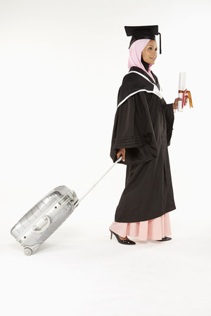 Woman in graduation robe going on vacation photo