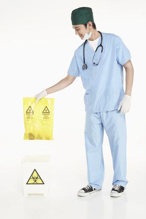 medical personnel: Medical personnel disposing biohazard waste
