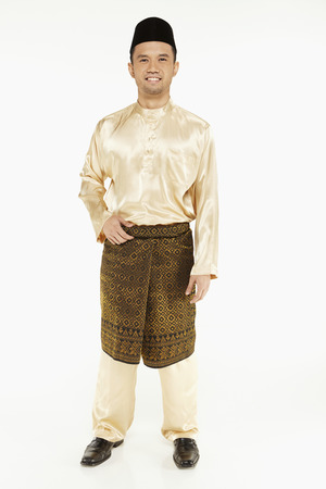 malay ethnicity: Man in traditional clothing, standing and smiling Stock Photo