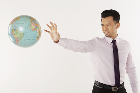 Businessman reaching out for the globe photo