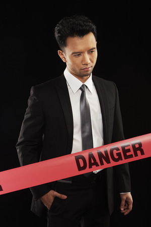 Businessman standing behind a Danger tape photo