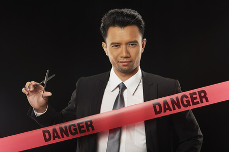 Businessman standing behind Danger tape, holding scissors photo