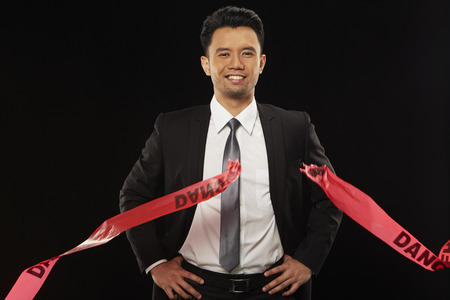 Businessman holding a torn Danger tape photo