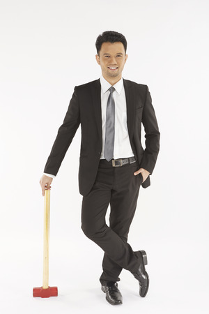 Businessman holding a hammer photo