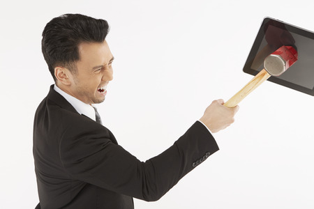 Businessman hitting a digital tablet with hammer photo