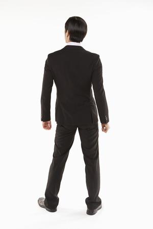 facing the camera: Businessman standing, back facing camera Stock Photo