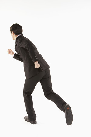 facing the camera: Businessman running, back facing camera