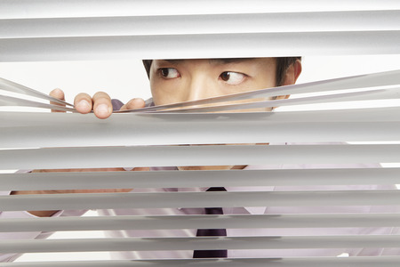 Businessman peeking through window blinds photo