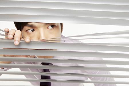 Businessman peeking through window blinds photo
