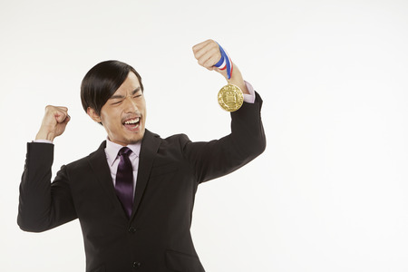 Businessman cheering while holding gold medal photo