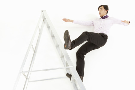 Businessman falling off a ladder photo