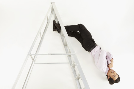 Businessman hanging upside down photo