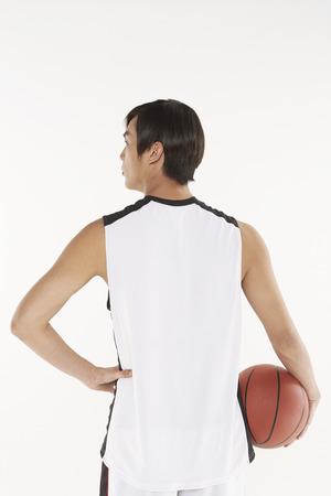 facing the camera: Man holding a basketball, back facing camera
