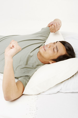 Man stretching on bed photo