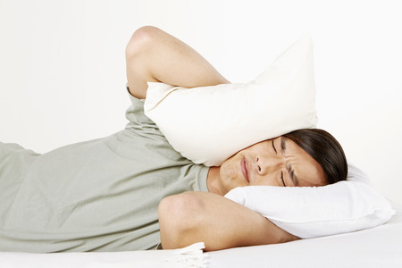 eyes closing: Man covering ears with pillow Stock Photo
