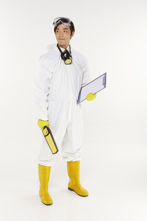 Man in protective suit holding a metal detector and clip board photo
