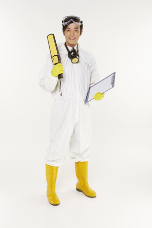 Man in protective suit holding a metal detector and clip board Stock Photo - 22833960
