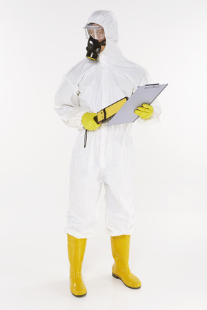 Man in protective suit with a metal detector Stock Photo