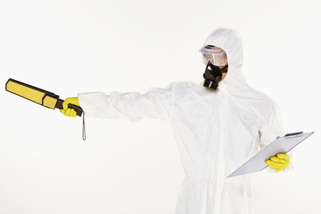 Man in protective suit with a metal detector, facing right photo