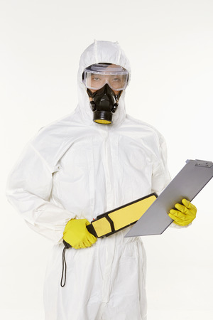 Man in protective suit with a metal detector photo