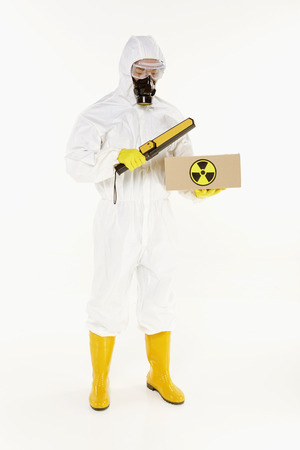 Man in protective suit inspecting a radioactive box