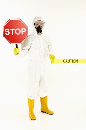 Man in protective suit holding a Stop sign photo