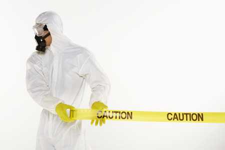 Man in protective suit rolling out the Caution tape photo
