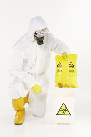 Man in protective suit disposing biohazard waste