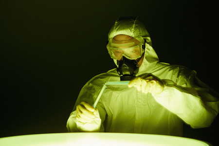 Man in protective suit mixing chemicals photo