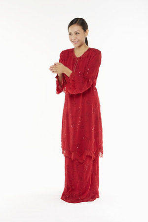 Woman in traditional clothing showing greeting gesture photo