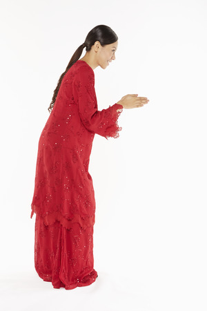Woman in traditional clothing showing greeting gesture Banco de Imagens