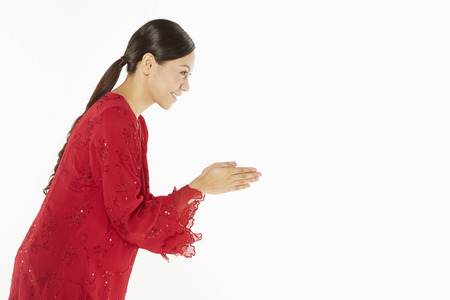 Woman in traditional clothing showing greeting gesture