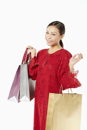 Woman in traditional clothing carrying shopping bags