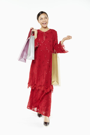 Woman in traditional clothing carrying shopping bags photo