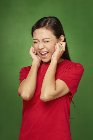 Woman covering ears using her hands Stock Photo - 22834285