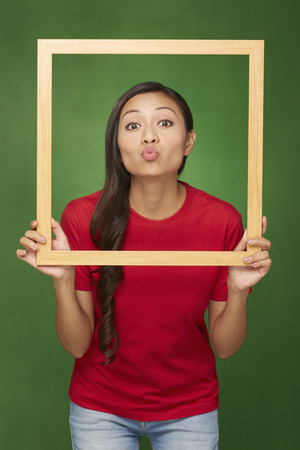 puckering: Woman holding up a wooden frame, puckering her lips Stock Photo