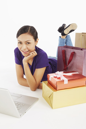 Woman with laptop and shopping items photo