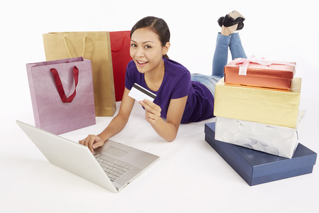 Woman holding a credit card while using laptop photo