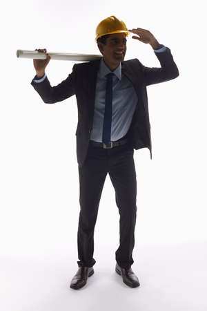 Businessman with construction helmet holding a roll of paper photo