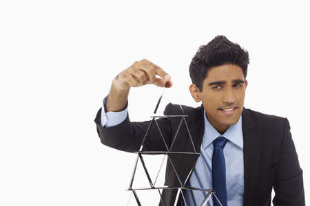 Businessman building a pyramid of cards photo