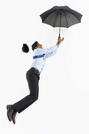 Businessman posing on the floor, holding an umbrella photo