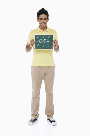 Man holding up a blackboard with an Idea word on it photo