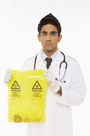 Medical personnel holding a bag of biohazard waste photo