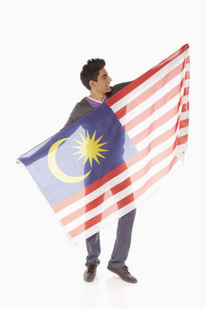 Man holding up a Malaysian flag photo