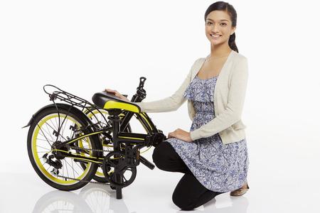 donna in ginocchio: Donna che si inginocchia accanto a una bicicletta piegata