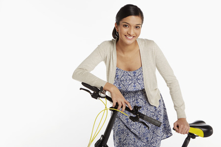 Woman standing beside a bicycle photo